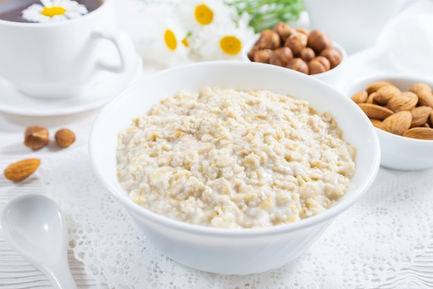 Oatmeal with nuts in bowl on white wooden table. Premium Photo