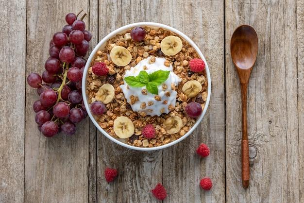 木製の背景にラズベリー、ブドウ、バナナとオートミール。ベリーと朝食のお粥。 Premium写真