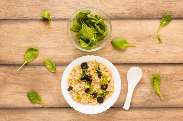 Oats garnished with basil leaf and olive for breakfast in bowl Free Photo
