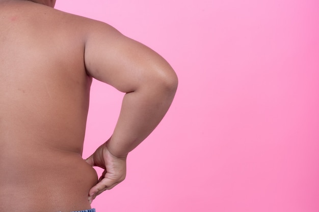 Obese boy who is overweight on a pink background. Free Photo