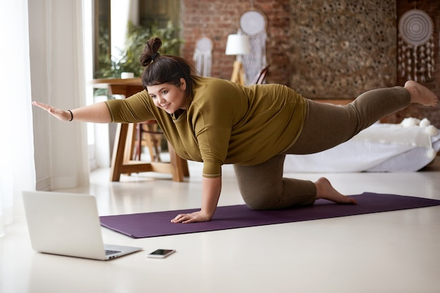 Obese chubby young european female with hair knot practicing yoga or pilates indoors on mat, doing exercises to strengthen core, watching video lesson online in front of open laptop computer on floor Free Photo