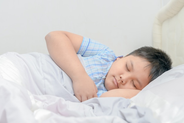Obese fat boy sleeping on bed, Premium Photo