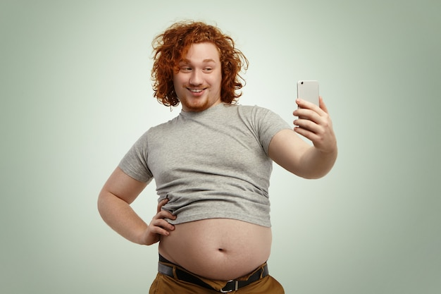 Obese young male with curly ginger hair and beard holding mobile phone, posing for selfie, looking with flirty smile while his fat belly hanging out of grey shrunk t-shirt and jeans pants Free Photo