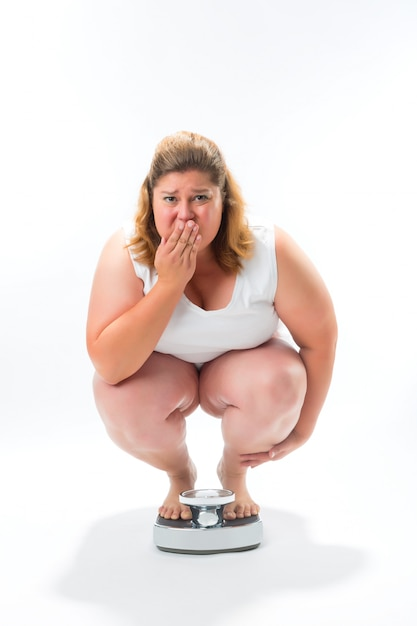 Obese young woman crouching on a scale Premium Photo