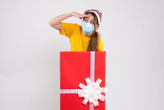 白の大きなクリスマスプレゼントの後ろに立っているサンタの帽子をかぶった女の子を観察 無料写真