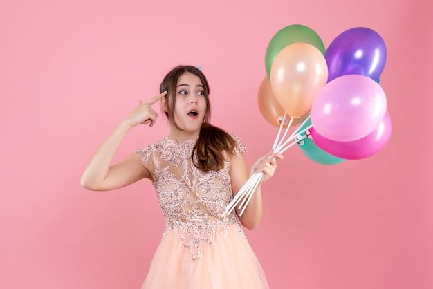 ピンクの風船を保持しているパーティーキャップを持つパーティーの女の子を観察 無料写真