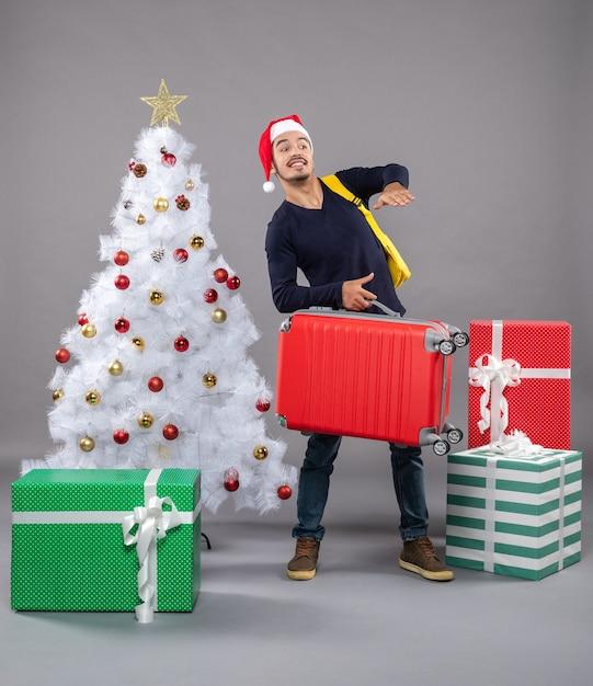 孤立した灰色の赤いスーツケースを持つ若い男を観察 無料写真