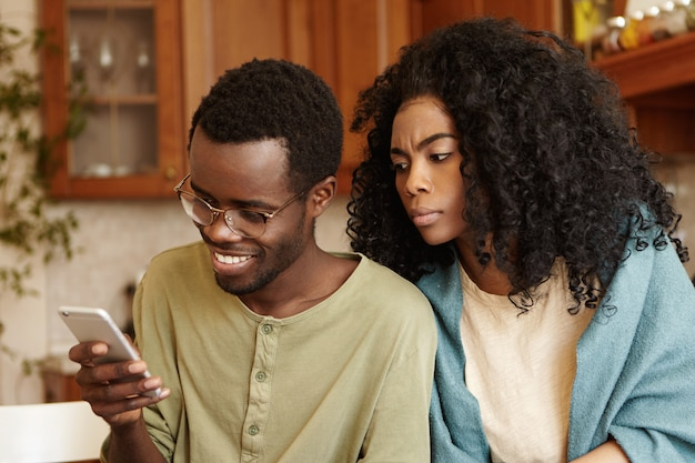 Obsessed possessive young afro-american female looking over her husband's shoulder, trying to read messages on his mobile phone. people, relationships, privacy, infidelity and modern technologies Free Photo