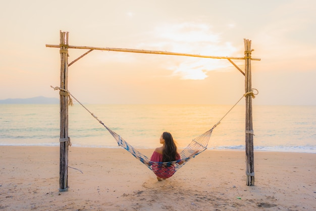 笑顔幸せなニアリービーチ海とoceでハンモックに座っている肖像画 無料写真