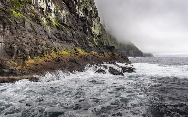 Oceano davanti a una montagna rocciosa sotto le nuvole cupe Foto Gratuite