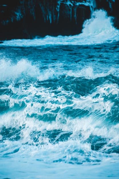 Океанские волны разбиваются о берег в дневное время Бесплатные Фотографии