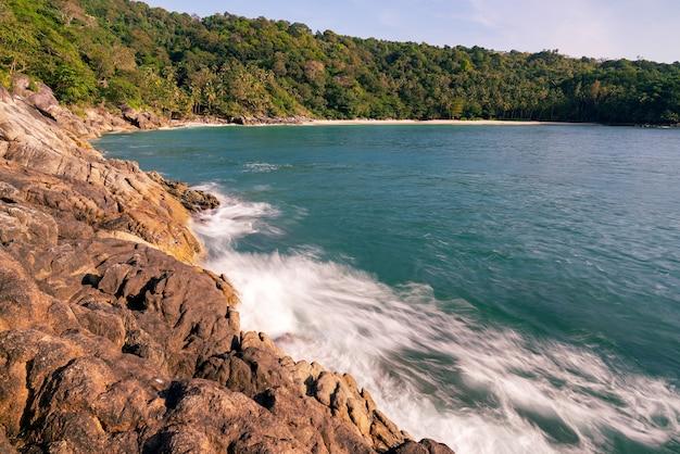 岩の多い海岸に打ち寄せる海の波、プーケットのビーチタイで海の波が水しぶきと白い泡に砕ける美しい海の自然の景色。 Premium写真