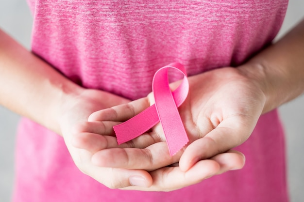 October breast cancer awareness month, woman in pink t- shirt with hand holding pink ribbon for supporting people living and illness. healthcare, international women day and world cancer day concept Premium Photo
