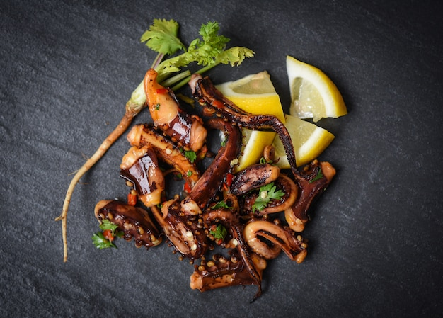 Octopus salad with lemon herbs and spices tentacles squid grilled hot and spicy chilli sauce seafood Premium Photo