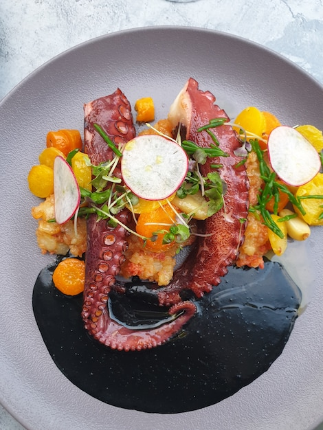 Octopus with vegetables with cuttlefish ink Premium Photo