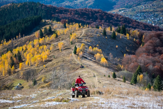 Off-road vehicle with guy on a mountain road passes to the top of the mountain Premium Photo