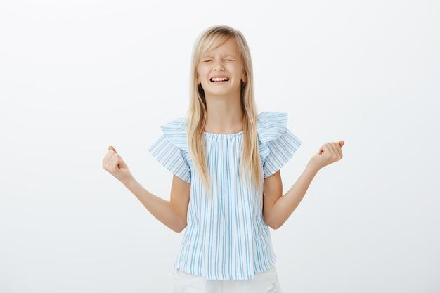 Обиженная маленькая девочка скулит и плачет, будучи непослушным. недовольная расстроенная маленькая дочь со светлыми волосами, сжимающая кулаки и зубы, спорящая о конфетах, стоящая над серой стеной Бесплатные Фотографии
