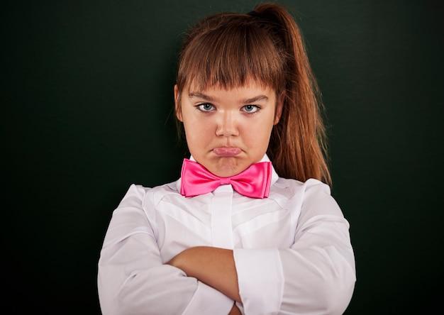 ピンクの蝶ネクタイで気分を害した少女 無料写真