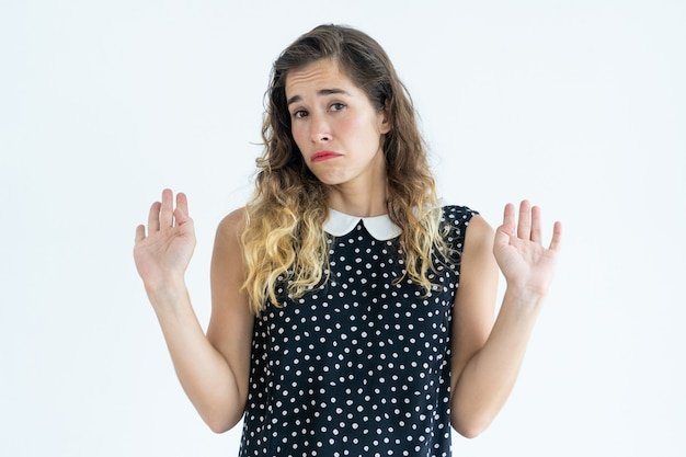 Offended woman looking at camera and raising hands. offence concept. Free Photo