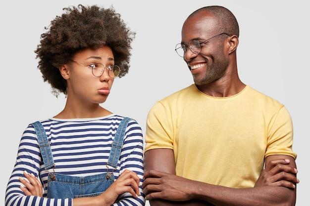気分を害した女性は唇を財布に入れ、腕を組んだまま、縞模様のシャツを着て、アフロの髪型をしています 無料写真