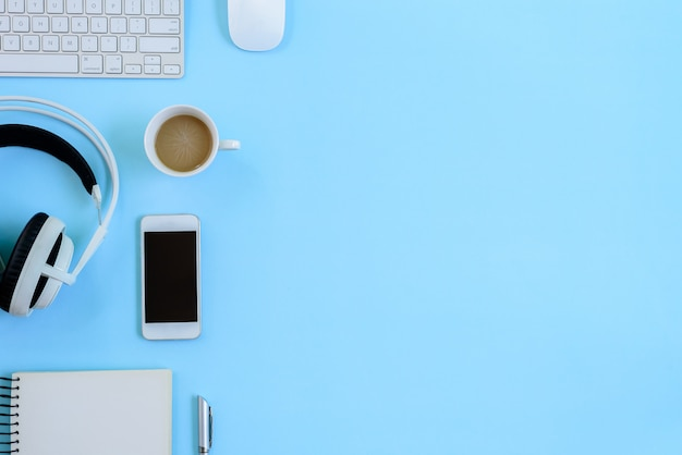 The office blue desk and equipment for working in top view and flat lay on blue background Premium Photo