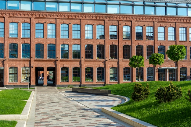 Office building of red brick in the courtyard of an old factory. several trees and a lawn. Premium Photo