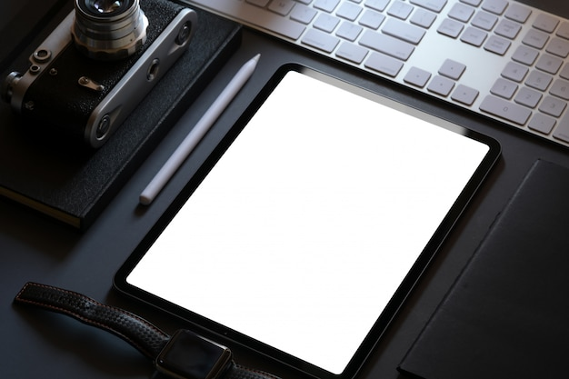 Office corporate mockup design with blank screen tablet on dark leather desk Premium Photo