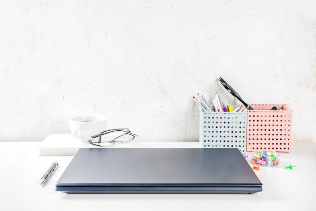 Office creative desk with supplies and coffee cup. white office table with laptop, keyboard, blank notebook, glasses, supplies and coffee cup. flatlay layout copy space top view Premium Photo