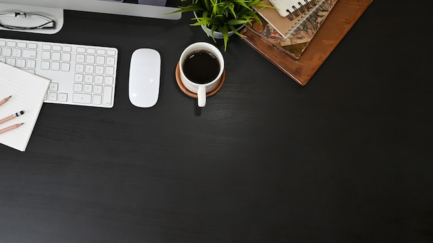 Office desk computer and office supplies with coffee on black table. Premium Photo
