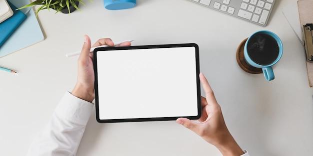オフィスデスクの手は白い作業机で白い空白の画面コンピュータータブレットを保持しています。 Premium写真