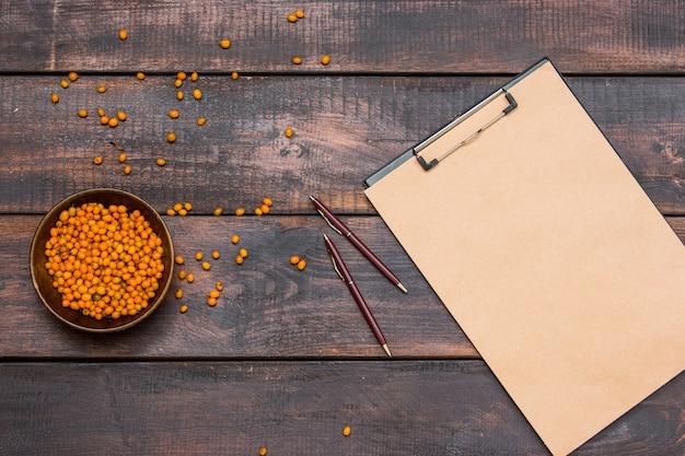 Стол офисный стол с ноутбука, свежие ягоды облепихи на деревянный стол Бесплатные Фотографии