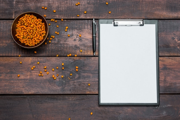 Office desk table with notebooks, fresh buckthorn berries on wooden table Free Photo