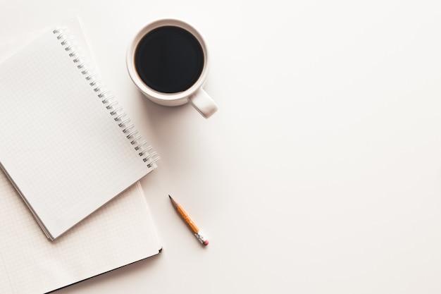消耗品、コーヒーカップ、花のオフィスデスクテーブル。コピースペースのある上面図 Premium写真