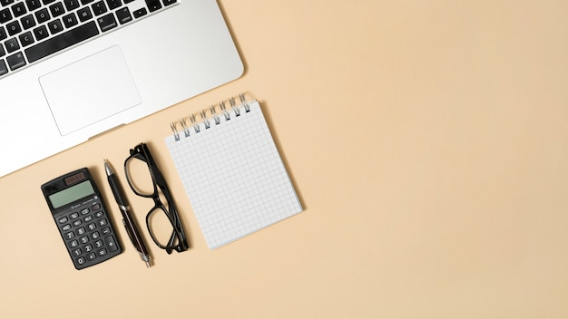Office desk with calculator and notepad; pen against beige backdrop Free Photo