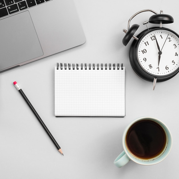 Office desktop with laptop and a clock Free Photo