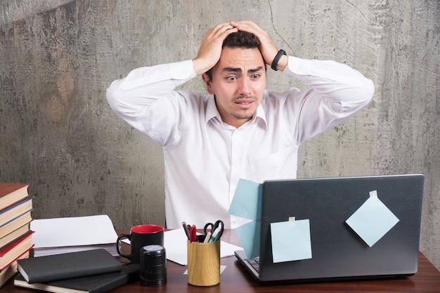 Impiegato di ufficio che tiene la sua testa con molto lavoro alla scrivania. Foto Gratuite