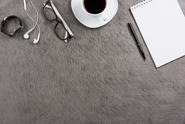 Office gray desk with earphone; eyeglasses; wrist watch; coffee cup; pen and blank spiral notepad Free Photo