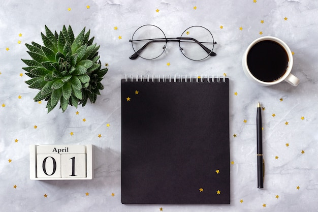 Office or home table calendar april 1st. notepad, coffee, succulent, glasses on marble background Premium Photo