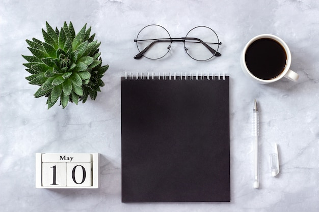 Office or home table, calendar may 10 notepad, coffee, succulent, glasses concept stylish workplace Premium Photo