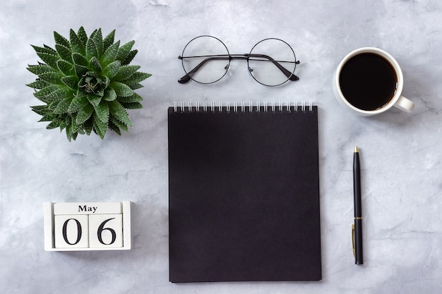 Office or home table, calendar may 6th. notepad, cup of coffee, succulent, glasses on marble Premium Photo