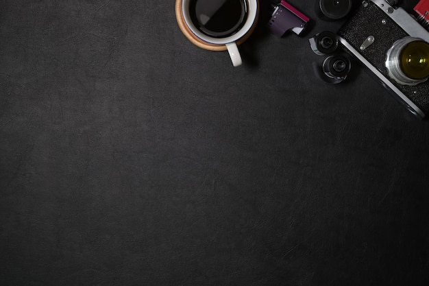 Office leather dark desk with vintage camera, films, coffee and copy space Premium Photo