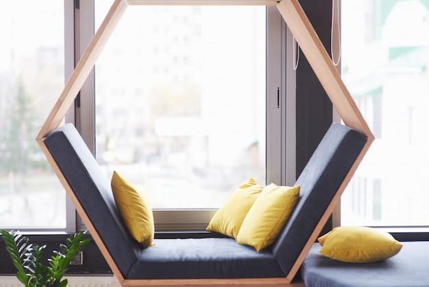 사무실 라운지 인테리어 사무실 건물 또는 카페, 창문 가까이 베개와 육각형 형태의 소파 의자 프리미엄 사진