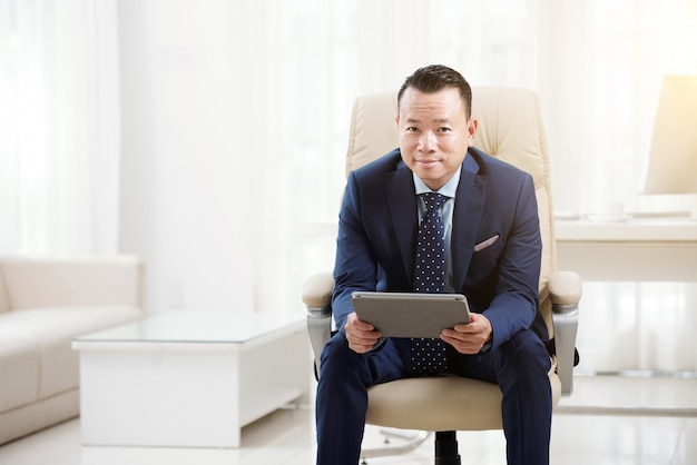 Office manager relaxing in his chair with digital pad looking at camera Free Photo