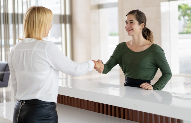 Office receptionist greeting corporate partner Free Photo