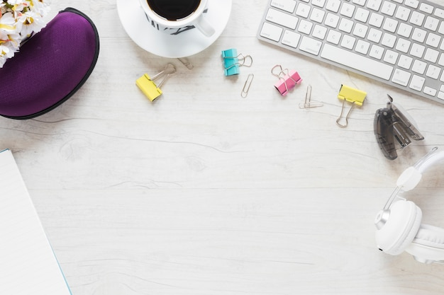 Office supplies; coffee cup; headphone and keyboard on white desk Free Photo