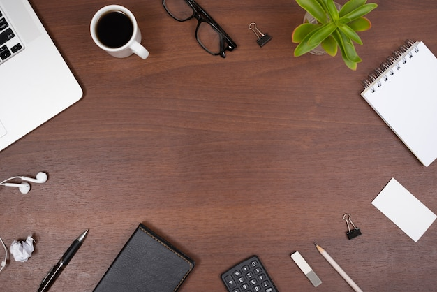 Office supplies; gadgets; cup of tea and plant with earphones on a wooden table Free Photo