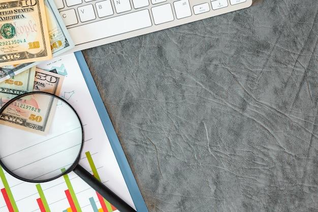 사무 용품, 돈, 문서, 회색 배경에 키보드. 레이블을위한 여유 공간. 프리미엄 사진