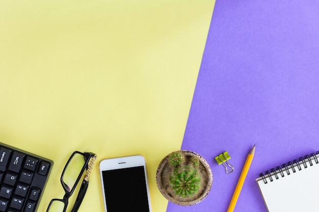 Office supplies on yellow and purple in top view Premium Photo