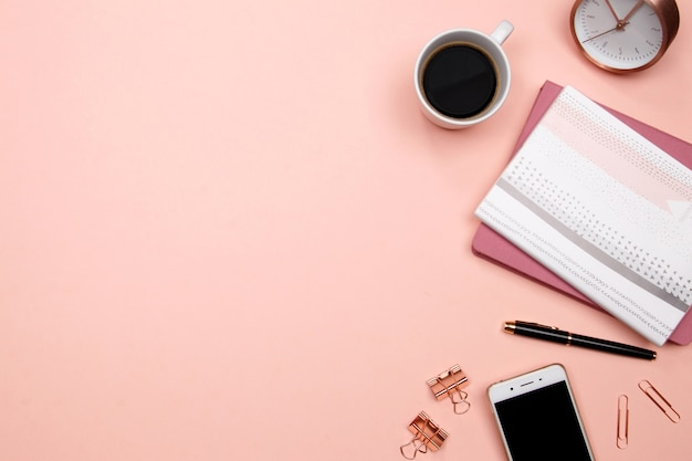Office table desk with smartphone and other office supplies on pink background. Premium Photo