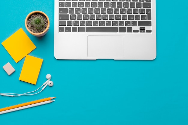 Office table desk with supplies on blue background, top view and copy space Premium Photo